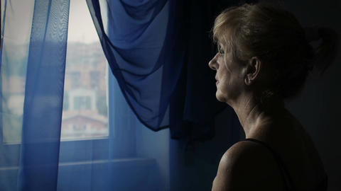 sad, upset and worried woman looking out of the window: problems, sadness Footage