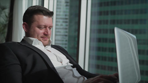 A businessman works remotely in his apartment. A businessman in a black suit Live Action