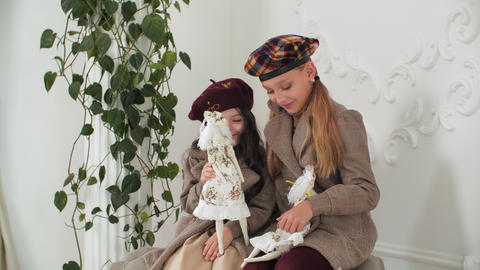 Adorable stylish girls in coats and berets posing with elegant vintage dolls Live Action