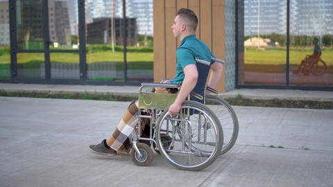 Young man in a wheelchair. A man rides in a wheelchair against the background of Live Action