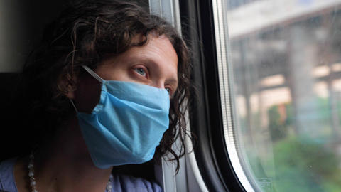 A tired middle-aged woman in a protective blue mask looks out the window of a train. Transport trip Live Action