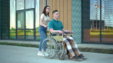 A young woman is carrying a young man in a wheelchair. An assistant carries a Live Action