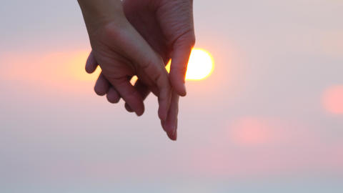 Close up of two lovers joining hands. Man and woman holding hands over the sunset blur background. Live Action