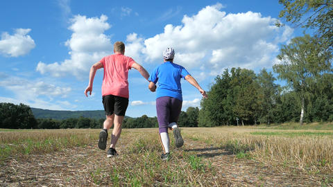 Adult sports heterosexual couple running hand in hand in autumn nature. Love sports activities Live Action