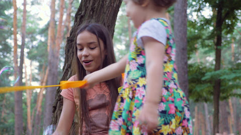 Older girl with black hair inflates soap bubbles and make little girl smiling outdoor in park. Live Action