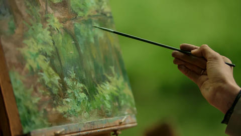Close-up of a lady's hand an artist with a brush making the finishing touches Live Action