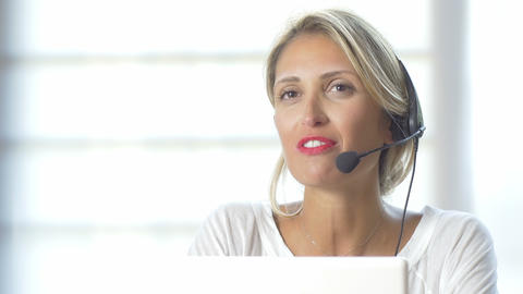 Close-up of smiling beautiful woman working in a call center: 4k footage Footage