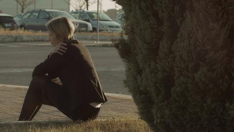 sad woman thinking alone to her problems near a street: sad, sadness Live Action