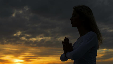woman deep in meditation at the sunset: yoga, spiritual, religion Live Action