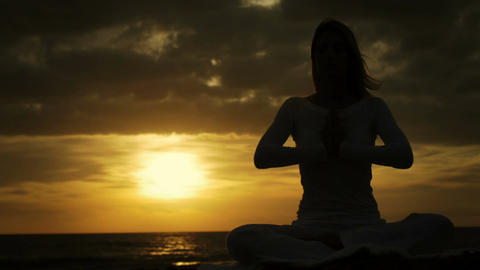 young beautiful woman is having meditation at the sunset: practicing yoga at Footage