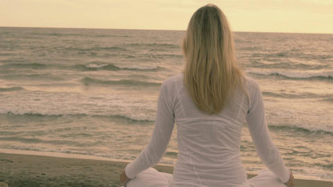 Young woman practicing yoga in sunflares on the beach at sunset Footage
