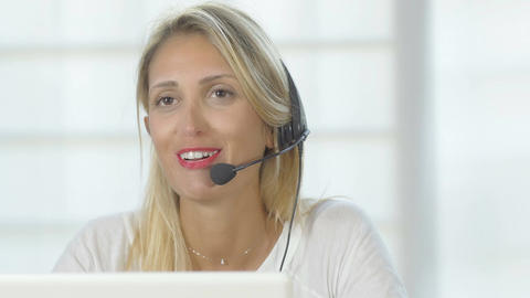 Happy smiling cheerful support phone operator in headset at office. 4K Footage