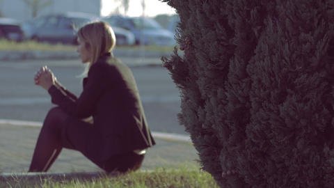 thoughtful sad girl sitting alone on a sidewalk: sadness, thoughts, problems Footage