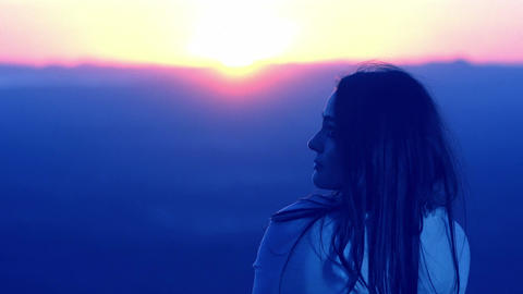 thoughtful woman is relaxing at the sunset: dusk, meditation, relaxation, peacef Live Action