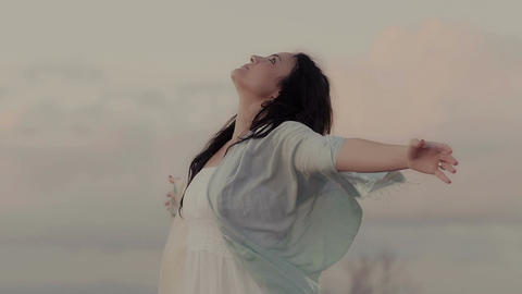 young woman in meditation opens her arms to the sky: relaxation, spirituality Live Action