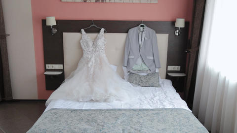 Beautiful stylish wedding jacket and dress on the bed Live Action