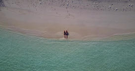 Romantic couple sunbathe on idyllic coast beach journey by blue lagoon with white sandy background Live Action
