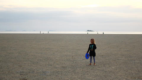 Little girl throwing sports equipment on the beach Live Action
