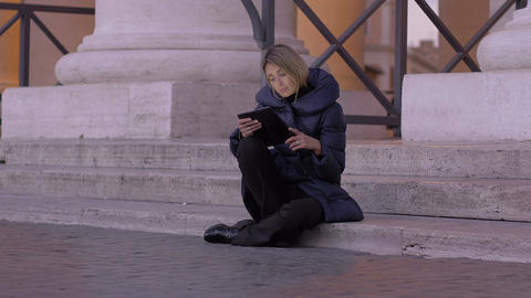 young woman using tablet pc sitting on the stairs of St. Peter square in Rome Footage