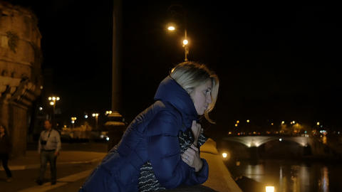 sad and pensive woman waiting on the river in Rome City center Live Action