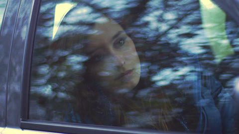 depressed and bored young woman sitting alone in a car: car window reflection Footage