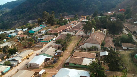 Aerial view over a rural small town in latin america with houses with roofs armed with clay bricks Live Action