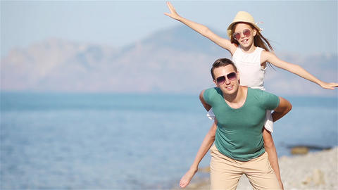 Little girl and happy dad having fun during beach vacation Live Action