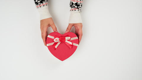 heart shaped cardboard gift box on white background, female hands holding a gift Live Action