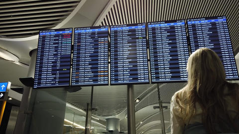 Woman in international airport looking at the flight information board Live Action