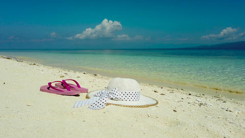 Hat and sandals on a sandy beach. Travel vacation concept Live Action