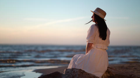Woman in dress relaxing sitting on a big stone in sea Live Action