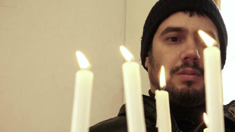 man in prayer insiede a church with candle light in foreground Footage