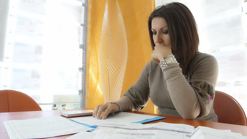 businesswoman at work with calculator and balance sheets: budget problems Live-Action