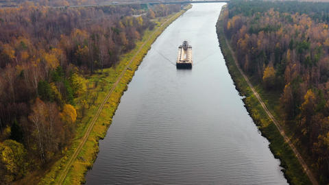 River tugboat moves cargo barge on the river. Autumn landscape Live Action