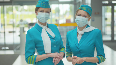 Portrait of two confident professional stewardesses in face masks standing in Live Action