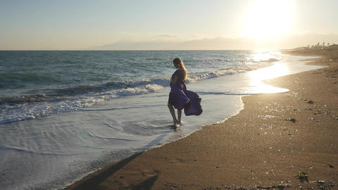Young woman in dress walking alone by the sea Live Action