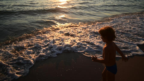 Young woman and her son come to water on sunset at sandy beach, island holidays Live Action