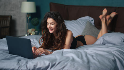 Sexy woman looking computer screen in bed. Playful girl using computer in bed Live Action