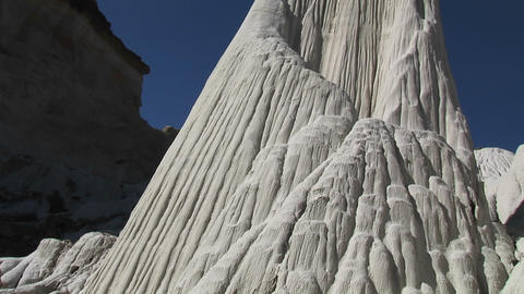 Pan-up a white limestone rock formation in a desert Footage