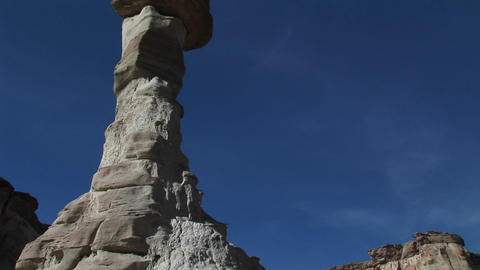 Pan-up a limestone rock formation in a desert canyon Stock Video Footage