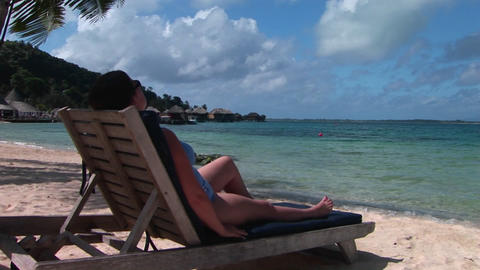 A woman relaxes on a beach chair on a tropical island paradise Live Action