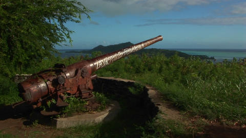 A World War two cannon sits rusting on a mountaintop on a remote Polynesian island Footage