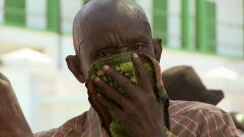 A refugee in Haiti covers his face following the d Footage