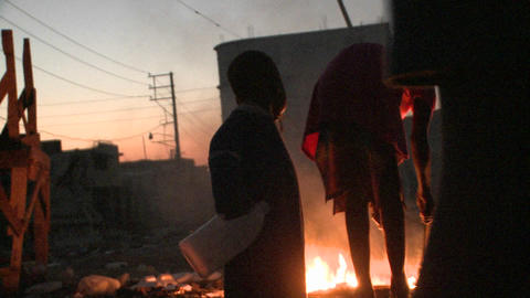 Children stand in front of a fire in a third world Stock Video Footage