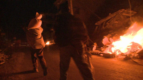 Open fires burn in a rough neighborhood in a third Stock Video Footage