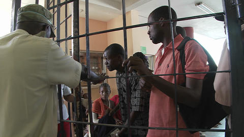 Haitians wait outside a metal gate for news of rel Footage
