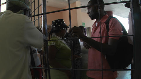 Haitians wait outside a metal gate for news of rel Stock Video Footage