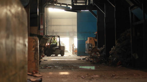 A skip loader picks up trash at a recycling center Footage