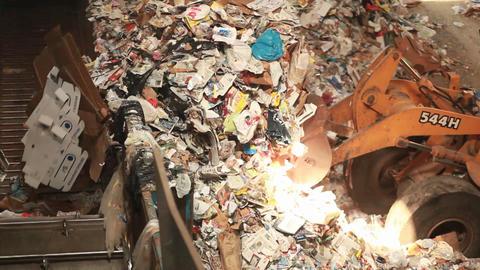 A skip loader shovels trash at a recycling center Stock Video Footage