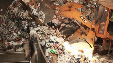 A skip loader shovels trash at a recycling center Footage